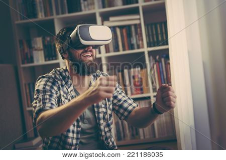 Young man enjoying his leisure time playing a driving simulation video game, wearing virtual reality glasses
