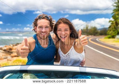 Car happy road trip young drivers driving in convertible cabriolet car. Smiling couple doing thumbs up on summer holiday road trip in new car. Interracial happy couple.