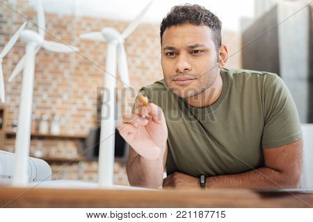Scrupulous worker. Clever enthusiastic hardworking engineer feeling interested while standing in front of a tiny miniature of a windmill turbine and looking attentively at it