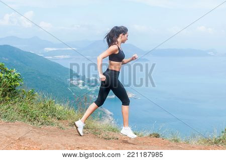 Cross-country female runner trail running on mountain path in summer. Woman wearing black sportswear exercising outdoors in wild nature.