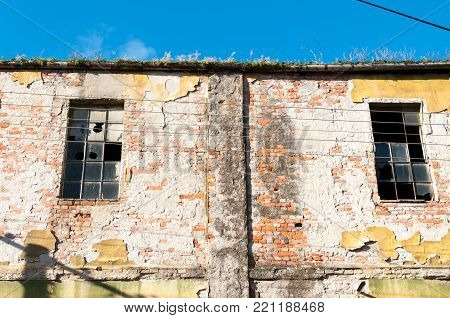 Abandoned factory. Old abandoned industrial factory warehouse building with brick wall broken windows and blue sky background