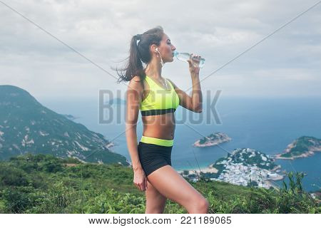 Female athlete, drinking water, listening to music in earphones, resting and recovering from running or exercising standing on top of the mountain against sea, islands and cloudy sky in background.