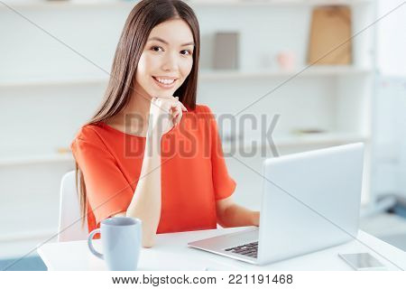 Effective freelancing. Dreamful nice ambitious woman  leaning on hand while gazing  at the camera and grinning