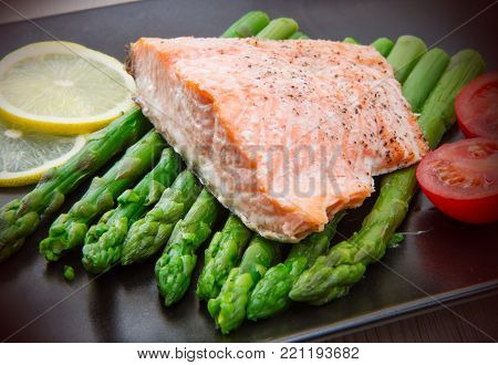 salmon fillet on asparagus bed on dish
