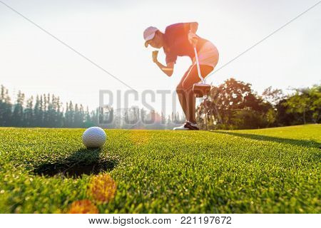 Asian woman golfer action to win after long putting golf ball on the green golf, sunset time, copy space.  Healthy Concept