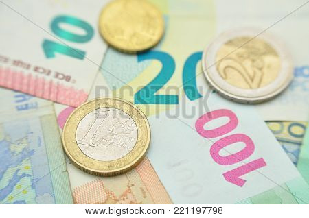 Euro coins over paper euro banknotes. Euro money banknote, business and finance concept