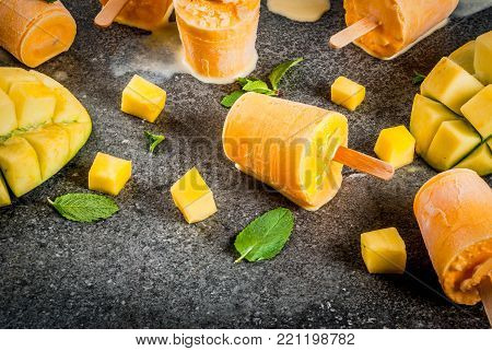 Ice cream, popsicles. Organic dietary foods, desserts. Frozen mango smoothie, with mint leaves and fresh mango fruit, on black stone table. Copy space  top view
