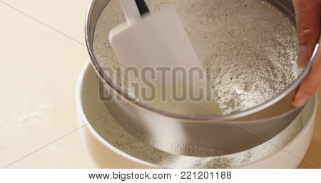 Stirring flour through sieve