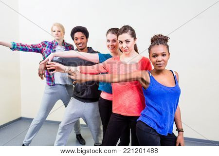 Group of happy young people having dance lessons