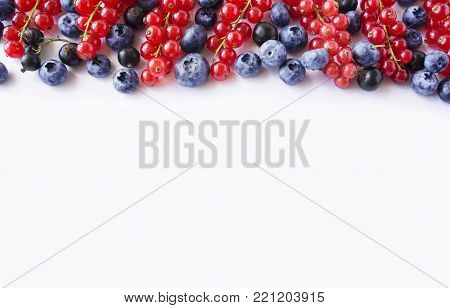 Black-blue and red food on a white. Ripe blueberries, red currants and black currants on a white background. Mixed berries at border of image with copy space for text. Black-blue and red berries and fruits. Various fresh summer berries on white background
