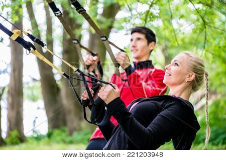 Sporty couple at sling trainer doing fitness in park