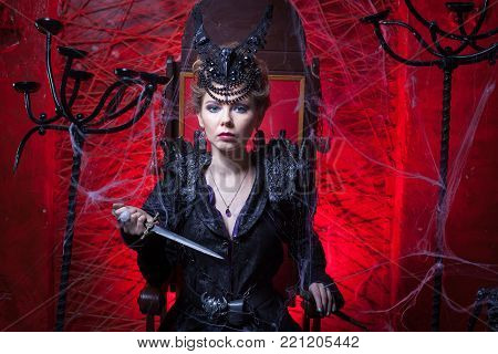 Woman in black sits on a throne and holds a dagger in her hands.