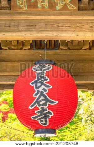 Kamakura, Japan - April 23, 2017: Closeup of famous traditional giant red lantern at main gate Sanmon of Hase-dera Temple or Hase-kannon. Hasedera is a popular landmark in Kamakura. Vertical shot.