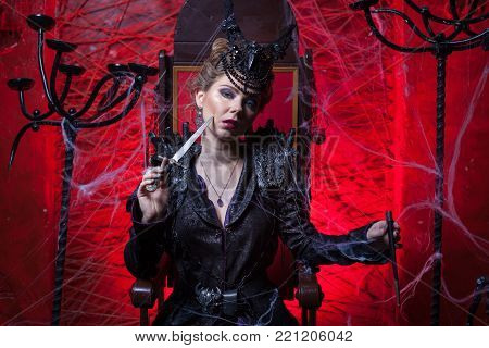 Woman is sitting in a dark room. She pressed the dagger to her cheek.