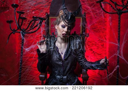 Woman in black sitting in a dark red room. She licks a dagger.