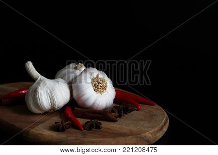 Kitchen still life with raw garlic bulbs, red chilli, cinnamon sticks and anise stars spice on wooden chopping board, black background, Allium sativum vegetable.