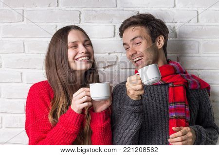 Young Cheerful Couple Laughing with a Warming Drink