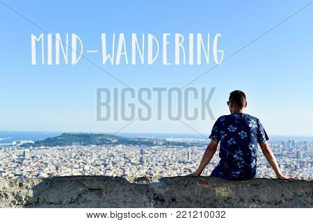 the text mind-wandering and a young caucasian man, seen from behind, at the top of a hill observing the city and the ocean below him