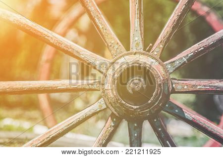 Closeup image of a vintage colored carriage wheels  with golden glow from the sun