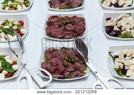 Plate of cold cuts with capers. Sliced meats in a white plate with capers on a white table. Meat with capers
