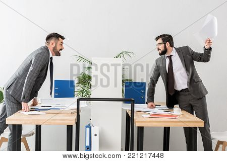 angry businessmen quarreling above partition in office