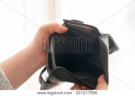 Empty black wallet in the hands of a young girl, the theme of poverty