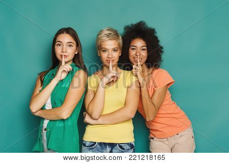 Three beautiful women in colourful clothes, keeping fingers at lips, asking to keep silence, not to disclose their secrets