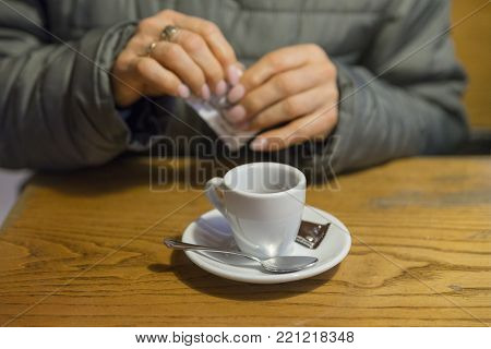 picture of a cup of coffee drank at the bar, behind the cup a sugar sachet is spreading.