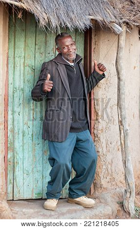 Happy senior with thumbs up in front of a shack beating poverty