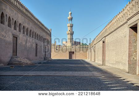 Cairo, Egypt - December 30, 2017: One of the passages surrounding Ibn Tulun mosque with minaret of Amir Sarghatmish mosque at far distance, Sayyida Zaynab district, Medieval Cairo, Egypt