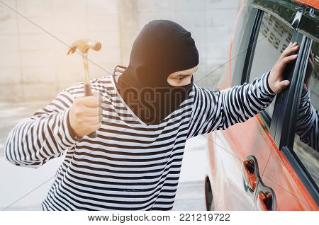 thief in black and white jacket using hammer to smashing car door window to stealing a car, break into the car, crime, robber and steal concept