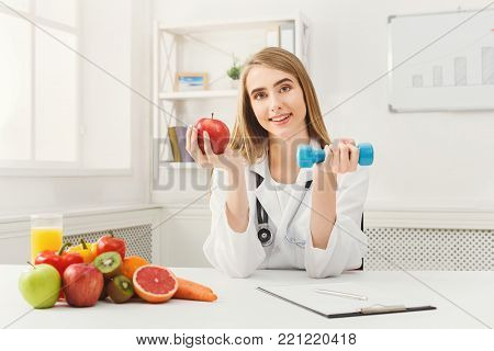 Young dietitian with apple and dumbbell at clinic. Smiling woman nutritionist holding fruit and sport equipment. Weight loss, healthy eating and slimming concept