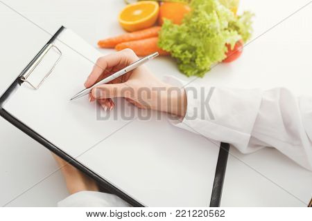 Nutritionist doctor writing diet plan on table. Unrecognizable dietitian making healthy eating menu, copy space for text. Right nutrition and slimming concept
