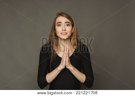 Portrait young woman gesturing with clasped hands, appealing or begging for something. Human emotion, facial expression, body language concept