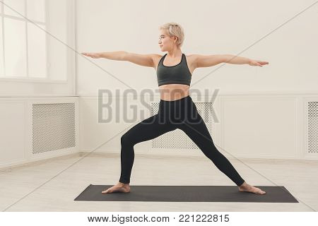 Fitness woman warmup stretching training at white background indoors. Young slim girl makes aerobics exercise, copy space