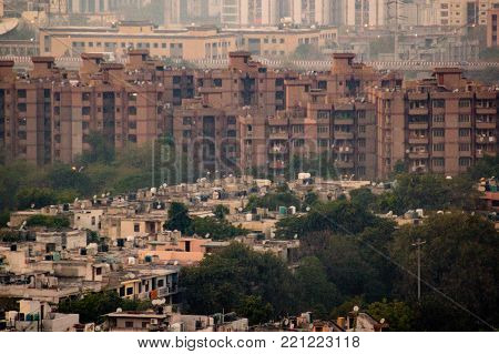 Aerial shot of housing apartments in Noida towering over old fashioned independent homes. These apartments are critical to house the ever growing population of the city
