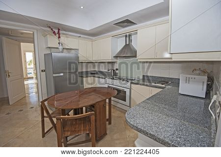 Kitchen and dining area in luxury apartment show home showing interior design decor furnishing with dining table