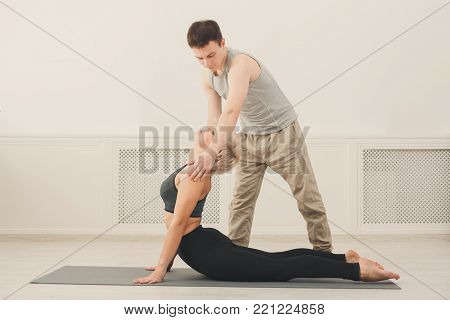 Yoga teacher and beginner in class, making asana exercises. Slim woman do back and shoulders stretching. Healthy lifestyle in fitness club. Stretching with coach, copy space