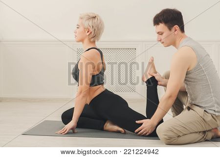 Yoga teacher and beginner in class, making asana exercises. Slim woman do legs stretching. Healthy lifestyle in fitness club. Stretching with coach, copy space