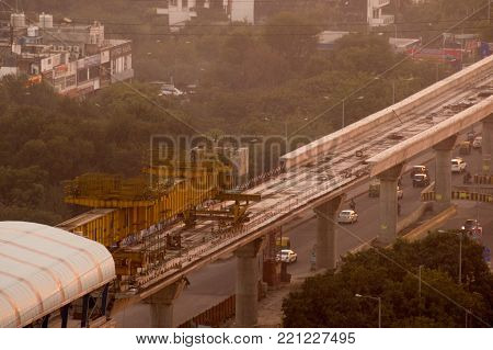 Aerial photograph of a metro track laying machine working on an under construction track in Delhi, Lucknow, bangalore. Shot on a foggy golden hour evening. The metro is a critical public transport initiative for Delhi