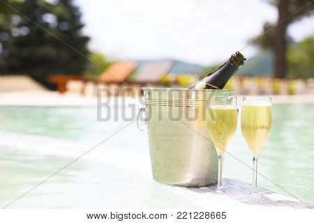 Champagne glasses and bottle in ice bucket near swimming pool. Vacation and romance concept
