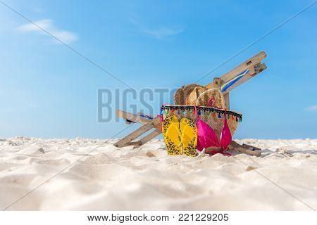Summer Travel. Bikini and Flip-flops ,hat, fish star and bag near beach chair on sandy beach against blue sea and sky background, copy space.  Summer vacation concept