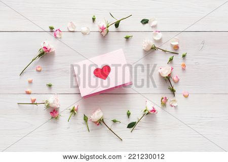 Valentine background with pink rose flowers circle and handmade paper card with heart on white rustic wood. Happy lovers day mockup. Valentine's day holiday concept