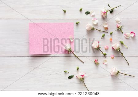 Valentine background, pink rose flowers and petals on white rustic wood, open empty greeting card, top view with copy space. Happy lovers day mockup. Valentine's day holiday concept