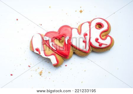 A bitten cookie for Valentine's day or for a wedding day and crumbs on a white background. Top view, flat lay, copy space.