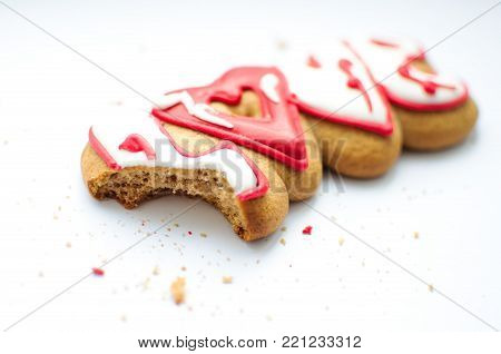 A bitten cookie for Valentine's day or for a wedding day and crumbs on a white background. Top view, selective focus, copy space.