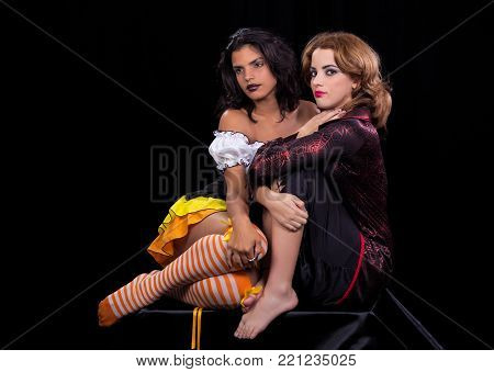 girl dressed as doll and another girl dressed as a witch both portrayed on black background