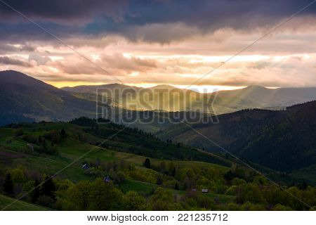 gorgeous mountainous countryside at sunset. beams of light break through heavy clouds. rolling hills with rural fields in the shade. spectacular springtime landscape