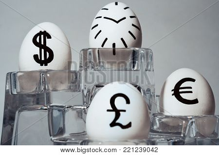 The inscription on chicken eggs for advertising and promotion of various currencies and crypto. Written or drawn symbols British pound sterling. dollar. Euro. One egg is painted as a dial.