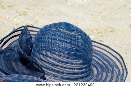 a large female thatched blue hat lies on a yellow sand casts a shadow from the sun a bright summer day relaxing beach